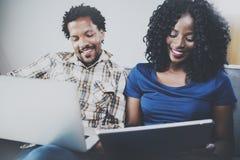 Främre sikt av lyckliga afrikansk amerikanpar som tillsammans kopplar av på soffan Ung svart man och hans använda för flickvän Royaltyfri Bild