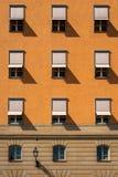 Främre sikt av många symmetriska fönster med solrullgardiner på en stenstadsbyggnad Royaltyfri Bild