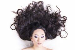 Främre sikt av modellståenden med svart hår över vit Arkivbilder