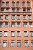 Främre sikt av modern hyreshus för tegelstenvägg med fönster fotografering för bildbyråer