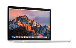 Främre sikt av roterande på en obetydlig vinkelApple MacBook Pro näthinna 15 med macOS-toppiga bergskedjan på skärmen arkivbilder
