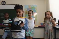 Främre sikt av skolpojken som rymmer och ser virtuell verklighethörlurar med mikrofon i klassrum arkivfoto