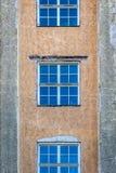 Främre sikt av tre symmetriska fönster på en stenstadsbyggnad Arkivfoto