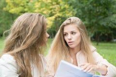 Främre sikt av två lyckliga studenter som studerar läsa anmärkningar royaltyfria foton