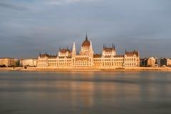 Främre sikt för lång exponeringssolnedgång av den ungerska parlamentet i Budapest i Ungern Arkivbild