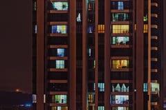 Främre sikt för natt av modernt höghus med fönster av hemtrevliga lägenheter i som ljusa sken och folk som gör rutinmässigt tunt Royaltyfri Fotografi