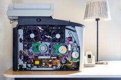 Främre slut upp inom av en maskin för kontorsefterapare Elektroniska delar och fans Stå på ett skrivbord med en tabelllampa royaltyfri fotografi