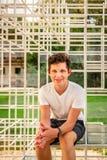 Främre stående av ett le sammanträde för tonårs- pojke på en stålram för abstrakt konst utomhus arkivfoto