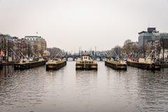 Främre stadssikt av slussportar som ses från vattnet med byggnader i bakgrunden i Amsterdam royaltyfria bilder