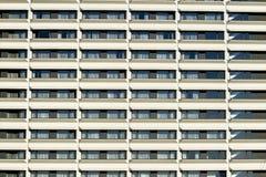 Främre vägg för modern byggnad med att upprepa modellen av fönster och balkongen för bakgrund Royaltyfri Foto