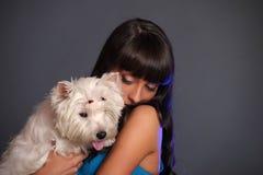 Främsta hållande vit terrierhund för vuxen kvinnlig royaltyfri bild