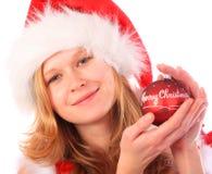 Fräulein Sankt hält eine rote Weihnachtsbaum-Kugel an Stockfotografie