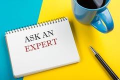 Fråga en expert Notepad med den meddelande-, penn- och kaffekoppen Kontorstillförsel på bästa sikt för skrivbordtabell royaltyfria bilder