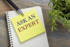 Fråga en expert Notepad med meddelandet, pennan, påminnelse och blomman Kontorstillförsel på bästa sikt för skrivbordtabell royaltyfri bild