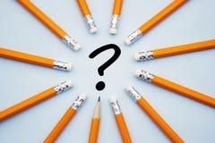 Frågefläck och gul blyertspenna över blå bakgrund Söka efter ett svar arkivfoto