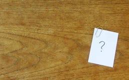 Frågefläck på en anteckningsbok med en paperclip på en trävägg royaltyfri foto
