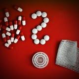 Frågefläck som göras av preventivpillerar på rött Royaltyfri Fotografi