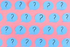 Frågefläckar är skriftliga på blåa klistermärkear i form av en bubbla Blått papper som klistras på en rosa bakgrund brigham royaltyfria bilder