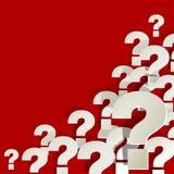 Frågefläckar som är vita i hörnet på en röd bakgrund Royaltyfri Foto