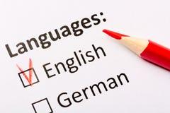 Frågeformulärbegrepp Språk med engelska och tyska checkboxes med den röda blyertspennan isolerade den täta hörlurarbilden för bla Royaltyfria Foton