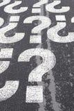 Frågetecken på asfalt Arkivfoto