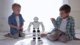 Frågvis Ñ- hildren ser flytta den humanoid roboten och punkt på den med ett finger på golv hemma lager videofilmer