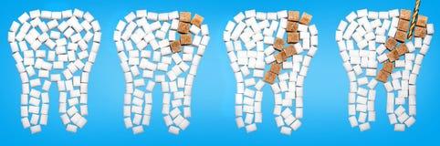 Från karies skadade tänder från socker mot en blå bakgrund arkivfoto