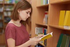 Från sidan skottet av den kvinnliga studenten för den allvarliga högskolan som fokuseras i bok, poserar i skolaarkiv, väljer nödv royaltyfri bild