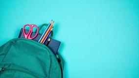 Från skolapåsen kommer ut böcker, blyertspennor och pennor Ställe för inskrift Stoppa rörelse stock video
