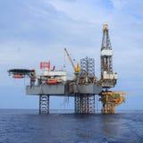 Frånlands- Jack Up Drilling Rig Over produktionplattformen Royaltyfri Foto