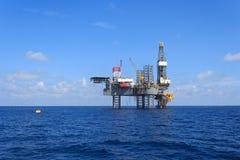 Frånlands- Jack Up Drilling Rig Over produktionplattformen Arkivbild