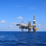 Frånlands- Jack Up Drilling Rig Over produktionplattformen Royaltyfri Bild