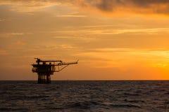 Frånlands- olja och riggplattform i solnedgång- eller soluppgångtid Konstruktion av produktionsprocessen i havet Maktenergi av vä Royaltyfria Foton