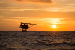 Frånlands- olja och riggplattform i solnedgång- eller soluppgångtid Konstruktion av produktionsprocessen i havet Maktenergi av vä Arkivfoton