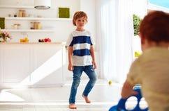 Frère aîné froncé les sourcils marchant au bébé junior à la maison Photos libres de droits