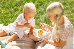Frère agréable et soeur mangeant les bonbons savoureux photographie stock libre de droits