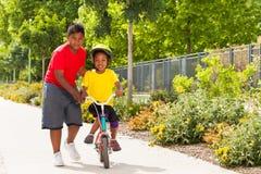 Frère aidant sa bicyclette d'équitation de soeur au parc Photo stock