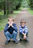 Frère deux sérieux s'asseyant sur le bord de la route Image libre de droits