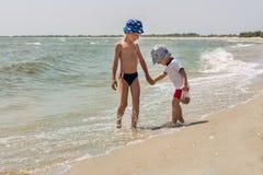Frère deux tenant des mains sur la plage jouant avec des vagues et rire, heureuses Photos libres de droits