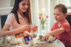 Frère et oeufs de pâques peints par soeur à la maison Photo libre de droits