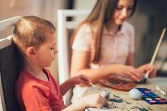 Frère et oeufs de pâques peints par soeur à la maison Image stock