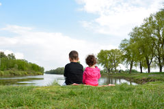 Frère et petite soeur s'asseyant sur la banque de la rivière. Image libre de droits