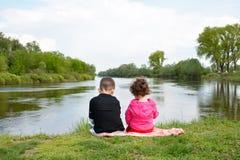 Frère et petite soeur s'asseyant sur la banque de la rivière. Photos stock