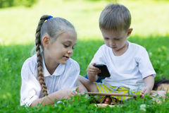 Frère et soeur à l'aide d'un smartphone et d'une tablette Photo stock