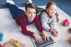 Frère et soeur à l'aide de l'ordinateur portable ensemble photo stock