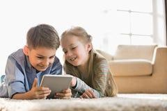 Frère et soeur à l'aide du comprimé numérique sur le plancher à la maison Images stock