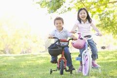 Frère et soeur à l'extérieur sur le sourire de bicyclettes image stock