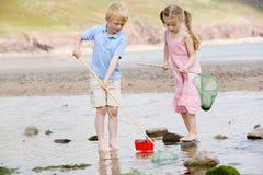 Frère et soeur à la plage avec les réseaux et le seau image libre de droits