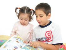 Frère et soeur affichant un livre sur l'étage Photographie stock libre de droits