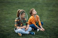 Frère et soeur avec des raquettes de badminton se reposant sur le champ vert Photographie stock libre de droits